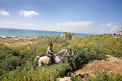 A young boy rides a horse along the Corniche, a walkway along the Mediterranean Sea, Beirut, Lebanon, March 26, 2006. Several horses are available for short rides near the water, a common leisure activity for less wealthy residents of Beirut.