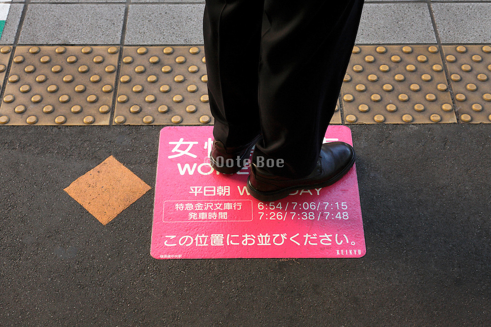 male person standing op top of platform sign mentioning that the carriage is only for women during curtain times of the day