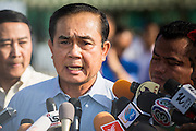 """11 JANUARY 2014 - BANGKOK, THAILAND: General PRAYUTH CHAN-OCHA, Commender in Chief of the Thai Royal Army, answers reporters' questions during a Children's Day fair in Bangkok. The Royal Thai Army hosted a """"Children's Day"""" event at the 2nd Cavalry King's Guard Division base in Bangkok. Children had an opportunity to look at military weapons, climb around on tanks, artillery pieces and helicopters and look at battlefield medical facilities. The Children's Day fair comes amidst political strife and concerns of a possible coup in Thailand. Gen Prayuth has issued mixed signal on a coup at one point saying there wouldn't be one, and later saying he wouldn't talk about a possible coup. Earlier in the week, the Thai army announced that movements of armored vehicles through Bangkok were not in preparation of a coup, but were moving equipment into position for Children's Day.      PHOTO BY JACK KURTZ"""