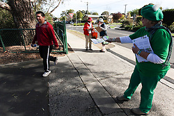 © Licensed to London News Pictures. 7/9/2013. Australian voter walks past a Greens volunteer holding out a how to vote card in the electorate of Chisholm during the Australian Federal Election. Photo credit : Asanka Brendon Ratnayake/LNP