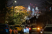 The glow of distant buildings overlooks a passing car and other parked vehicles in a dark residential street in Herne Hill, south London on 21st January 2021, in London, England.
