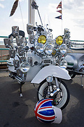 Vespa scooter on display on Brighton's seafront esplanade on Bank Holiday weekend. Fitted to the frame of the bike are many headlights and mirrors that is the cultural ephemera of the British mod subculture of the 1960-70s. Locked to the front wheel is a beautifully painted helmet with a union jack flag design. Focused on music and fashion, mods have their roots in a small group of London-based stylish young men in the late 1950s who were termed modernists because they listened to modern jazz. Traditionally they gathered at seaside towns on the south coast, like Brighton where clashes with Rockers was a Bank Holiday weekend tradition.