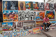 Independent grassroots art market in Havana new town Vedado, a painter sits in front of his pictures with them on sale.