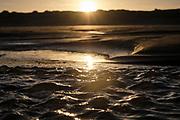 Small waves on the beach due to the changing of the tide in the morning sun. | Kleine golfjes aan het strand door wisseling van getijde in de ochtedzon.
