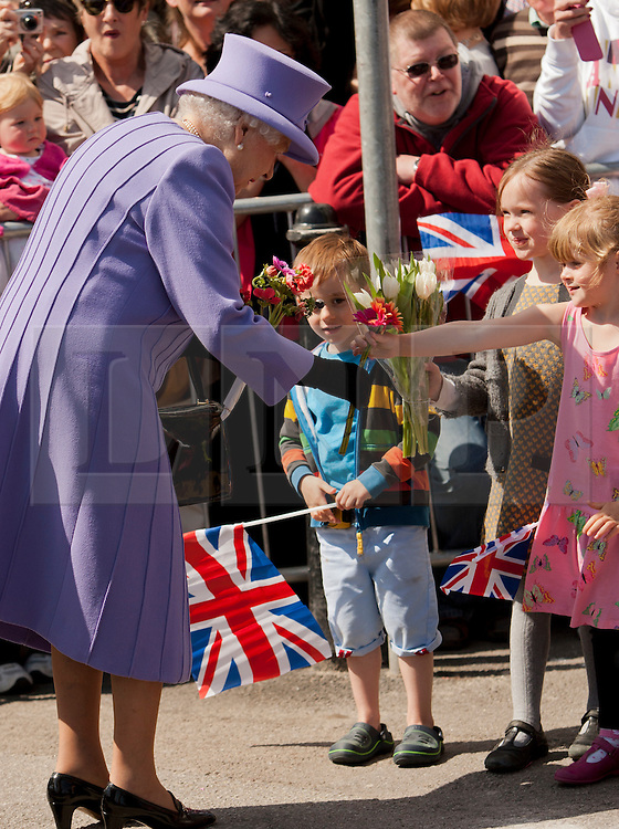 © Licensed to London News Pictures. 17/05/2013. St Ives, UK. Queen Elizabeth II receives flowers from children during visit to St Ives. Photo credit : Ashley Hugo/LNP