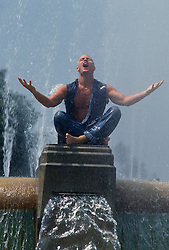 Man sitting on a fountain enjoying the water