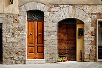 Photo of neighboring doorways along the street in San Quirico d'Orcia, Italy.