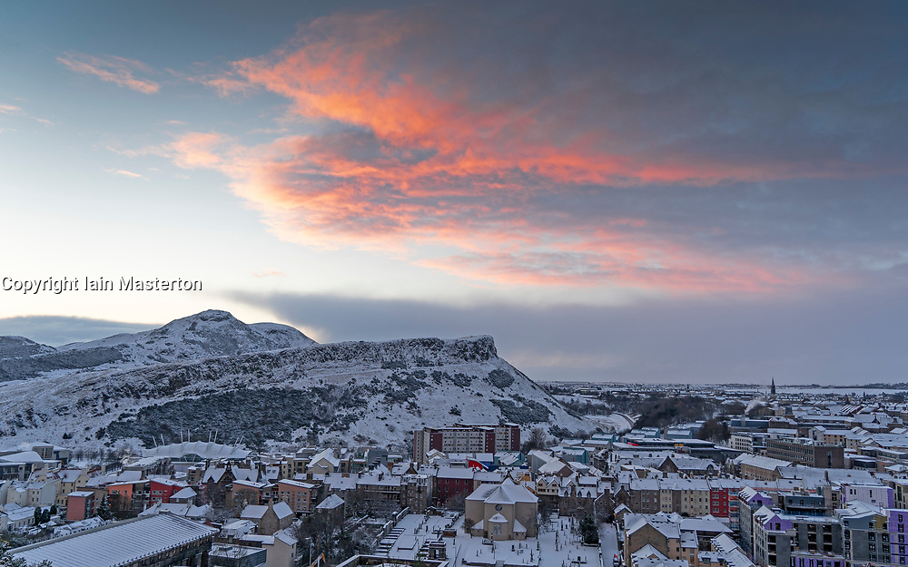 Edinburgh, Scotland, UK. 9 Feb 2021. Big freeze continues in the UK with Storm Darcy bringing several inches of snow to Edinburgh overnight. Pic; Red skies at sunrise over Arthurs Seat and Salisbury Crags. Iain Masterton/Alamy Live news