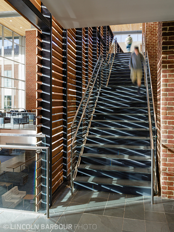 A detail of a stairwell with interesting light coming through it and students moving through the scene.  Inside the Liberty Student Center