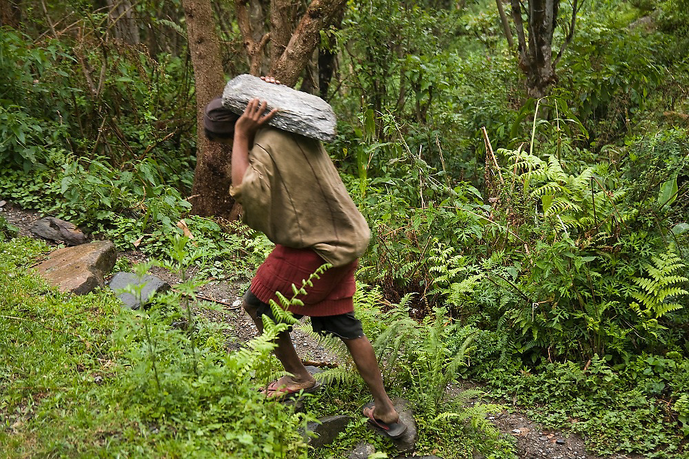 A man carries a stone slab on his shoulder to Landruk, Annapurna Himalaya, Nepal as part of an initiative by the local committee to renovate the trail through the village.