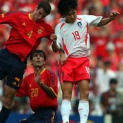 Spain's Ivan Helguera challenges Republic of Korea's Jung Hwan Ahn