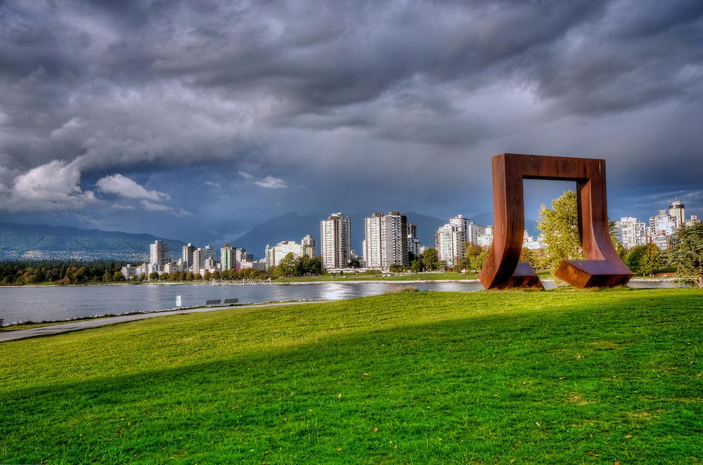 """Description from Wikipedia: Gate to the Northwest Passage is a 1980 sculpture by Alan Chung Hung, located adjacent to the Vancouver Maritime Museum in Vanier Park in the Kitsilano neighbourhood of Vancouver, British Columbia, Canada. The 4.6-metre (15 ft) sculpture of a square, cut and twisted """"like a paper clip"""" to form an arch, is composed of weathered Corten steel that rusts to provide a protective layer. The work was installed in 1980 to commemorate the arrival of Captain George Vancouver in Burrard Inlet, following a competition sponsored by Parks Canada one year prior. Gate to the Northwest Passage received an adverse reaction initially, but reception has improved over time. The sculpture has been included in walking tours of the surrounding neighborhoods as a highlight of Vanier Park."""