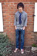 Model released teenage boy portrait standing against a wall, UK