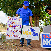 Dewayne Young and Regina Lane Haycock, right, set up signs in support of NGS outside the Navajo Department of Education in Window Rock Monday.