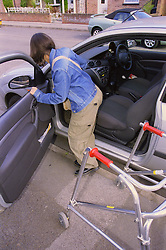 Teenage girl with physical disability getting into car,