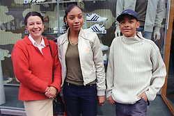 Single mother standing outside shop in town centre with teenage daughter and son,