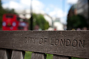 Bench in a small park at St Paul's in the City of London with the location carved into the wood.
