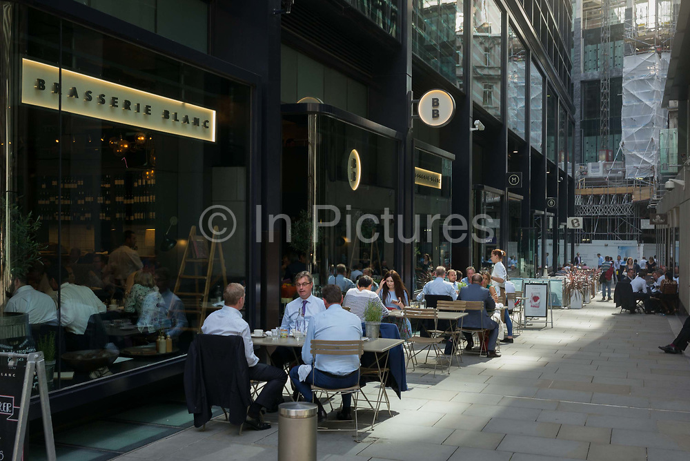City workers eat lunch outside at Brasserie Blanc during an unusual autumn heatwave on 13th September 2016, in the City of London, England.