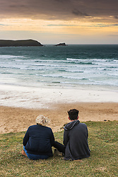 Two teenagers sitting overlooking Fistral Beach as the sun starts to set. Newquay, Cornwall