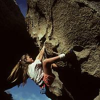 ROCK CLIMBING. Robin Jensen (MR) boulders hard overhang, Buttermilk Rocks, near Bishop, CA.