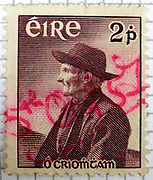 """Irish postage stamp issued in 1957 to commemorate author Tomás Ó Criomhthain [Tomas O'Crohan]. Stamp cancelled by hand, dated """"5th Oct '57""""."""