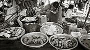 Monochrome photograph of a woman cooking vegetables in Nan Pan Market, Inle Lake, Myanmar