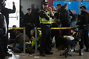 As environmental activists protest about Climate Change during the occupation of City Airport Londons Business Travel hub in east London, police officers process the arrested inside the termional building on the fourth day of a two-week prolonged worldwide protest by members of Extinction Rebellion, on 10th October 2019, in London, England.