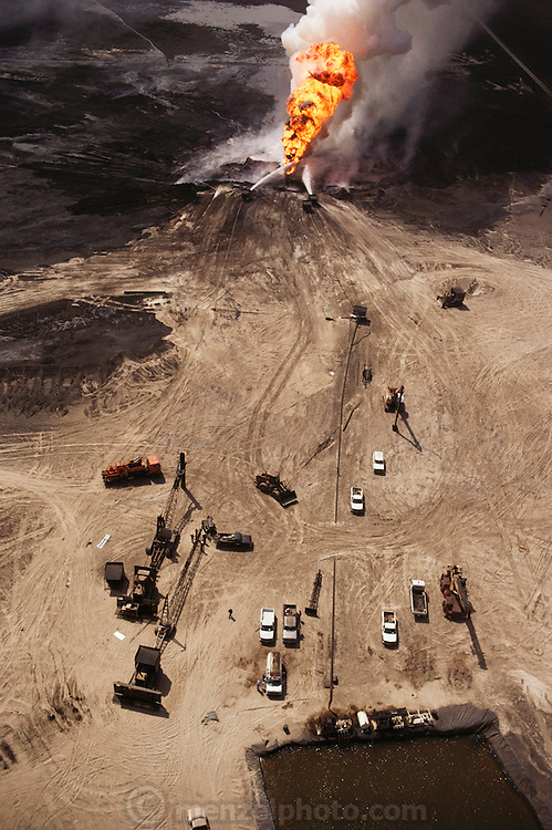 An aerial of the devastated desert landscape in the burning greater Al Burgan oil fields in Kuwait after the end of the Gulf War in May of 1991. The sand has been coated with oil from more than 700 wells that were set ablaze by retreating Iraqi troops creating the largest man-made environmental disaster in history. Firefighting equipment has been moved in to begin the process of extinguishing this burning well.