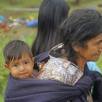 """A grandmother carries her grandson as they watch the first-ever """"gringo"""" tourists to visit Yamblon, Peru."""