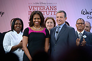 First lady Michelle Obama, front left, stands with Disney Chairman and CEO Robert Iger, front right, and veteran cast members before addressing attendees of Disney's Veterans Institute jobs forum in Lake Buena Vista, Fla., Thursday, Nov. 14, 2013.(AP Photo/Phelan M. Ebenhack)