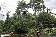 Hampshire Police Marine Support Unit officers and National Eviction Team enforcement agents monitor Swan, a female environmental activist from HS2 Rebellion sitting on a line above the river Colne secured to an ancient alder tree which she was seeking to protect from destruction, during works for the HS2 high-speed rail link on 24th July 2020 in Denham, United Kingdom. A large security operation involving officers from the Metropolitan Police, Thames Valley Police, City of London Police and Hampshire Police as well as the National Eviction Team ensured the removal of the tree by HS2 despite protests by activists.