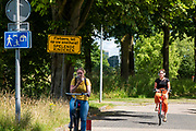Bij de Utrechtse wijk Lunetten rijden fietsers door een woonerf, als deel van een omleidingsroute. Omdat geregeld te hard wordt gefietst staat er een waarschuwingsbord. In een woonerf mag slechts stapvoets gereden worden.<br /> <br /> In Utrecht cyclists ride in the district Lunetten.