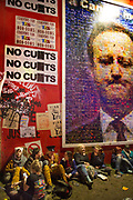 Glastonbury Festival, 2015. Shangri La is a festival of contemporary performing arts held each year within Glastonbury Festival. The theme for the 2015 Shangri La was Protest. <br /> 6am, end of the party, tired party revellers are watched over by a huge poster of the prime minister, David Cameron.