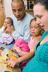 Young family reading books together at home,