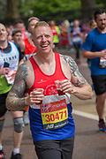 A smiling man running with two pints of ale on Birdcage Walk during The Virgin London Marathon on 28th April 2019 in London in the United Kingdom. Now in it's 39th year, the London Marathon is a large sporting event with over 40,000 runners expected to take part.