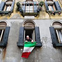 VENICE, ITALY - MARCH 16: A man hangs an Italian National Flags outside his window ahead of the celebrations for the 150th anniversary of Italy's unification on March 16, 2011 in Venice, Italy. March 17th has been declared National Festivity and events to celebrate the 150th anniversary will run in several Italian cities until the end of the year. (Photo by Marco Secchi/Getty Images)
