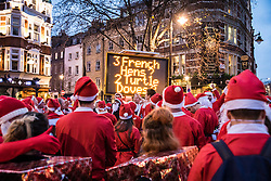 © Licensed to London News Pictures. 10/12/2016. London, UK. Hundreds of Santas gather on Camrbdieg Circus in front of a display as thousands descend on central London for the annual Santacon Parade. Photo credit: Rob Pinney/LNP