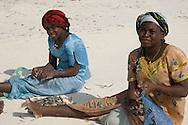 Local women in colourful dress sorting clams on the beach.  Paje, Zanzibar, Tanzania