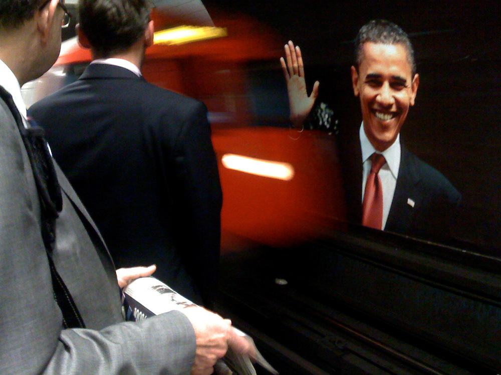 London.  October 15, 2008.  A billboard of a waving Barack Obama greets rush hour commuters and the blur of an oncoming train on the Vauxhall Underground platform.