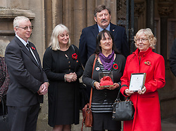 © Licensed to London News Pictures. 23/10/2015. Bristol, UK.  23/10/2015. Bristol, UK. Relatives of Bristol Poppy seller Olive Cooke at an event outside Bristol Cathedral, organised by the Royal British Legion, receive a ceramic poppy in memory of Olive from the Blood Swept Lands and Seas of Red exhibition.  L-R: John Hupfeld (Family friend), Linda Cooke (Olive's step grand-daughter-in-law), Kathryn King (daughter), Carol Balson (step-daughter), and behind David Lowe - south West Midlands area manager of the Royal British legion.  Photo credit : Simon Chapman/LNP
