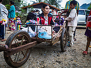 26 OCTOBER 2016 - NUPO TEMPORARY SHELTER, MAE CHAN, TAK, THAILAND:  A disabled woman sits in her cart, waiting to be repatriated to Myanmar. Sixtyfive Burmese refugees living in the Nupo Temporary Shelter refugee camp in Tak Province of Thailand were voluntarily repatriated to Myanmar. About 11,000 people live in the camp. The repatriation was the first large scale repatriation of Myanmar refugees living in Thailand. Government officials on both sides of the Thai / Myanmar border said the repatriation was made possible by recent democratic reforms in Myanmar. There are approximately 150,000 Burmese refugees living in camps along the Thai / Myanmar border. The Thai government has expressed interest several times in the last two years in starting the process of repatriating the refugees.    PHOTO BY JACK KURTZ