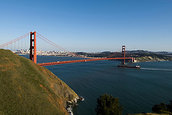 California: Container ship passing under Golden Gate Bridge, view of Golden Gate Bridge and city from Marin Headlands.  Photo # 3-casanf78381. Photo copyright Lee Foster.