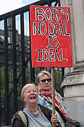 A female Brexiter holds a red placard saying Boris No Deal Is Ideal outside Houses of Parliament on the first day after summer recess on 3rd September 2019 in London in the United Kingdom. MPs return to Westminster for a Brexit shutdown that could result in a general election.