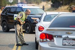 July 18, 2017 - Mariposa County, California, U.S. -California Highway Patrol officer BRANDON LONG, left, turns away motorists attempting to drive down Hornitos Road near the Hornitos Road and Highway 140 intersection in Catheys Valley, Calif., as fire crews continue to battle the Detwiler fire. (Credit Image: © Andrew Kuhn/The Merced Sun Star via ZUMA)