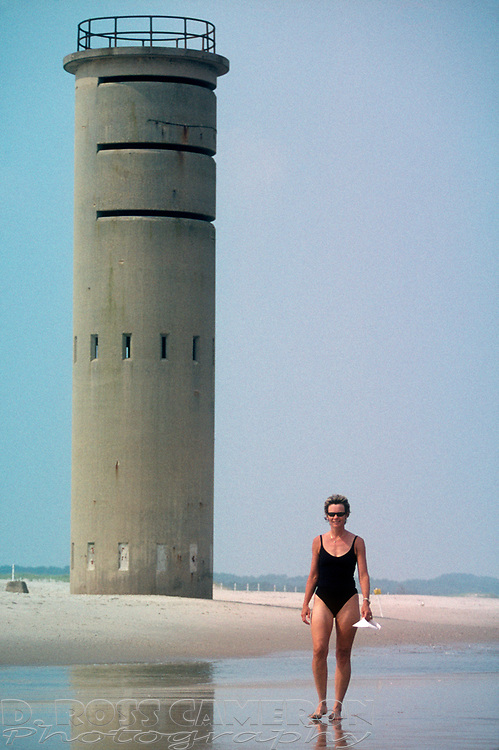 Jacquelyn C. Del Galdo walks along the strand near one of the World War II-era observation towers that still stand at Cape Henlopen State Park; August 2001, in Rehoboth Beach, Del. (Photo by D. Ross Cameron)