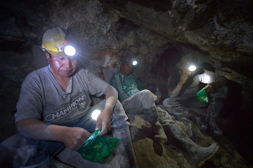 Miners take a break to chew coca leaves inside a mine in Potosi, Bolivia. The mine produces silver and other metals. Coca leaves depress hunger.