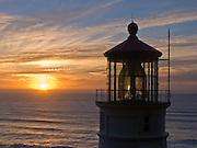 """Heceta Head Lighthouse at sunset in winter, at Heceta Head Lighthouse State Scenic Viewpoint, on the Oregon coast, USA. Here, the Siuslaw Indians traditionally hunted sea lions and gathered sea bird eggs from offshore rocks. While seeking to extend Spanish hegemony in the late 1700s, Spanish explorer Bruno de Heceta mapped the mouth of the Columbia River and much more along the Pacific Northwest coast; and in 1862, the US Coast Survey named Heceta Head in his honor. Built atop a 56-foot tower in 1893, this Lightstation's coastal safety beacon was first illuminated in 1894. Perched 205 feet above the ocean, its fresnel lens focuses the brightest light on the Oregon coast, visible up to 21 miles out to sea. Heceta Head is found halfway between Yachats and Florence (2.1 miles south of Carl Washburne State Park). From the large parking lot, walk 1 mile round trip to the Lighthouse. (Heceta Head Lighthouse State Scenic Viewpoint was created in the 1990s by combining Heceta Head State Park with the former Devils Elbow State Park at the scenic cove at the mouth of Cape Creek.) Published in """"Light Travel: Photography on the Go"""" by Tom Dempsey 2009, 2010."""