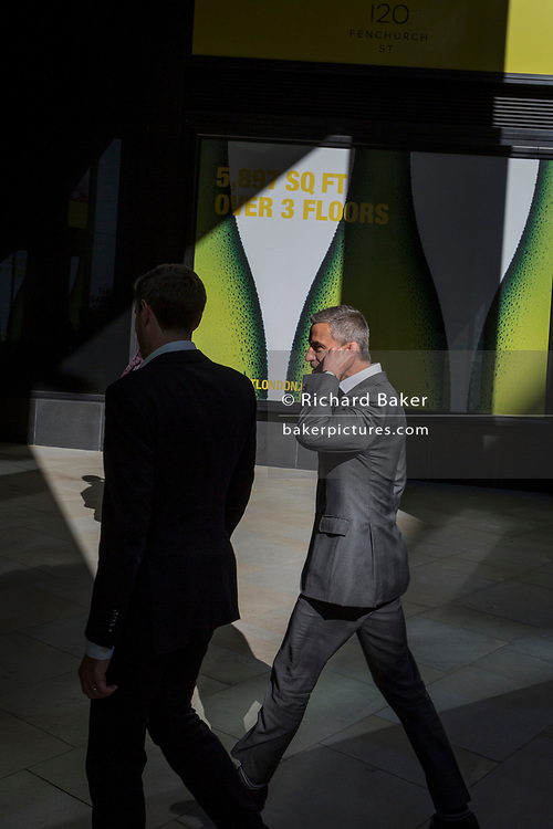 Business people walk through sunlight in the City of London, the capital's financial heart (aka The Square Mile), on 26th September 2018, in London, England.