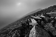 On the summit in dark swirling cloud. A delicate sun glimmered through the vapour, illuminating shards of quartz-covered, shattered wet rock. <br />