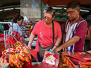 """03 FEBRUARY 2016 - BANGKOK, THAILAND:  People for Chinese New Year mementos before Chinese New Year in Bangkok. Thailand has the largest overseas Chinese population in the world; about 14 percent of Thais are of Chinese ancestry and some Chinese holidays, especially Chinese New Year, are widely celebrated in Thailand. Chinese New Year, also called Lunar New Year or Tet (in Vietnamese communities) starts Monday February 8. The coming year will be the """"Year of the Monkey.""""            PHOTO BY JACK KURTZ"""